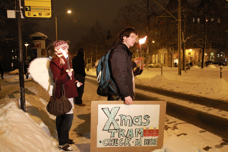 """EIn Mann hälz neben einer Haltestelle ein Schild in der Hand auf dem """"X-MAS Tram Check In"""" zu lesenist. Neben ihm steht eine Frau mit Engelsflügeln"""