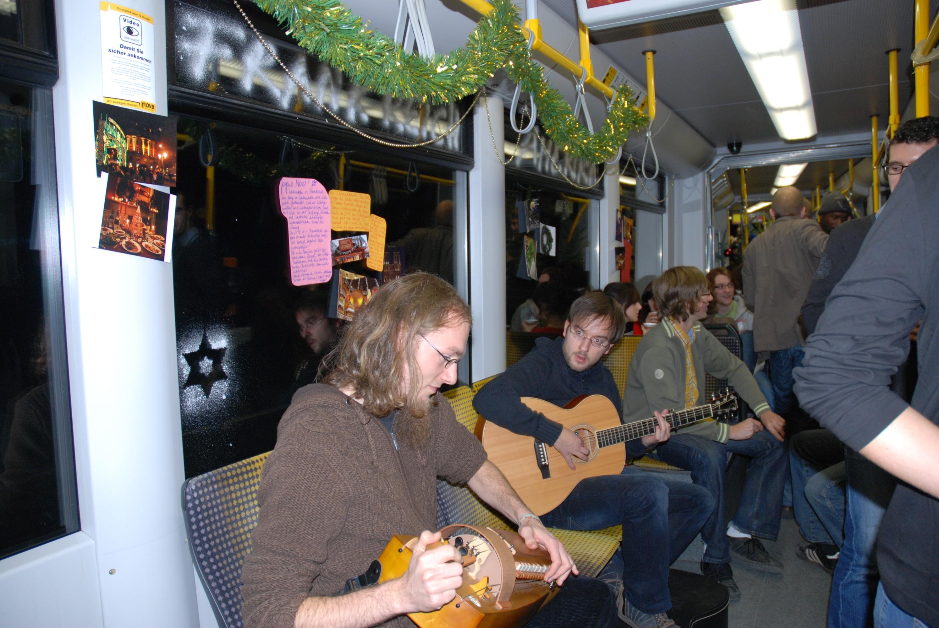 In einer Straßenbahn kommen die Menschen zusammen. Auf den Bänken wird Musik gespielt, während im Hintergrund geschwatzt wird.