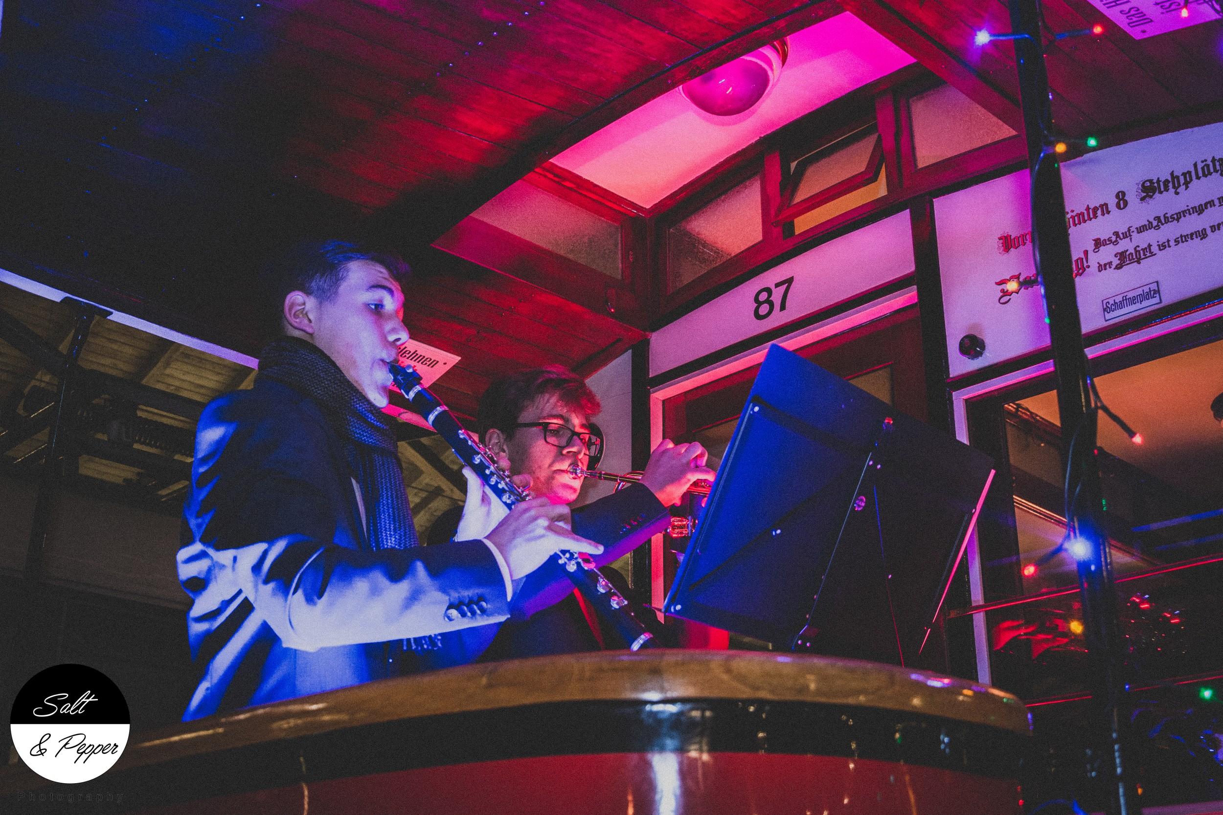 Auf einer Flöte und einer Trompete wird Musik in der X-MAS Tram gespielt
