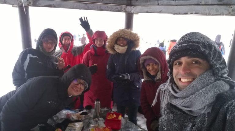 Unter einem Unterstand sind Teilnehmer der X-MAS Tram zusammengekommen. Sie sind alle in warme Wintermäntel eingemummelt und lächeln in die Kamera.