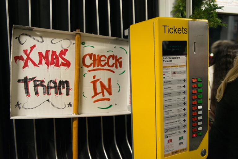 """Neben einem Fahrkartenautomaten ist ein Schild aufgestellt auf dem """"X-MAS Tram Check In"""" zu lesen ist."""