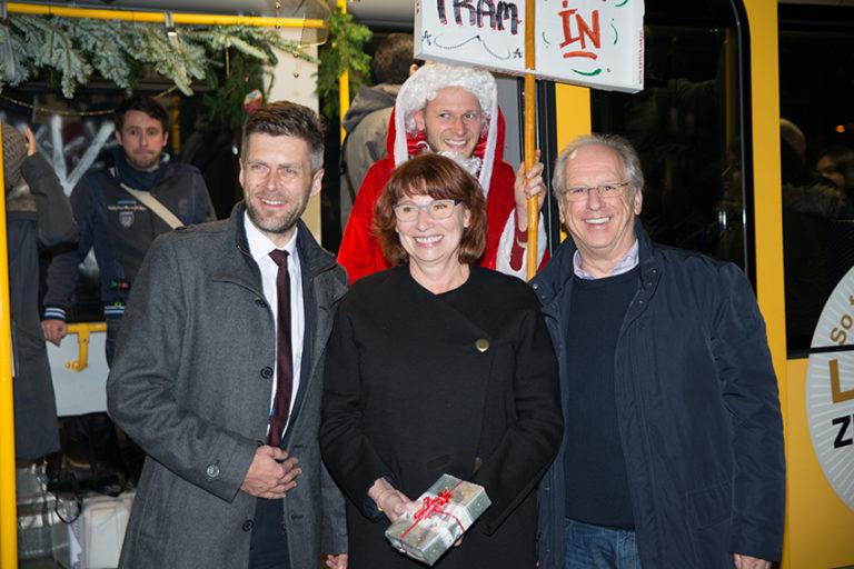 Die Sponsoren, Paten und Helfer finden sich vor der weihnachtlichen Straßenbahn zusammen